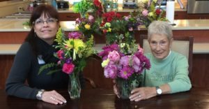 DCR, Laura Volz and Azura resident arrange flower bouquets.